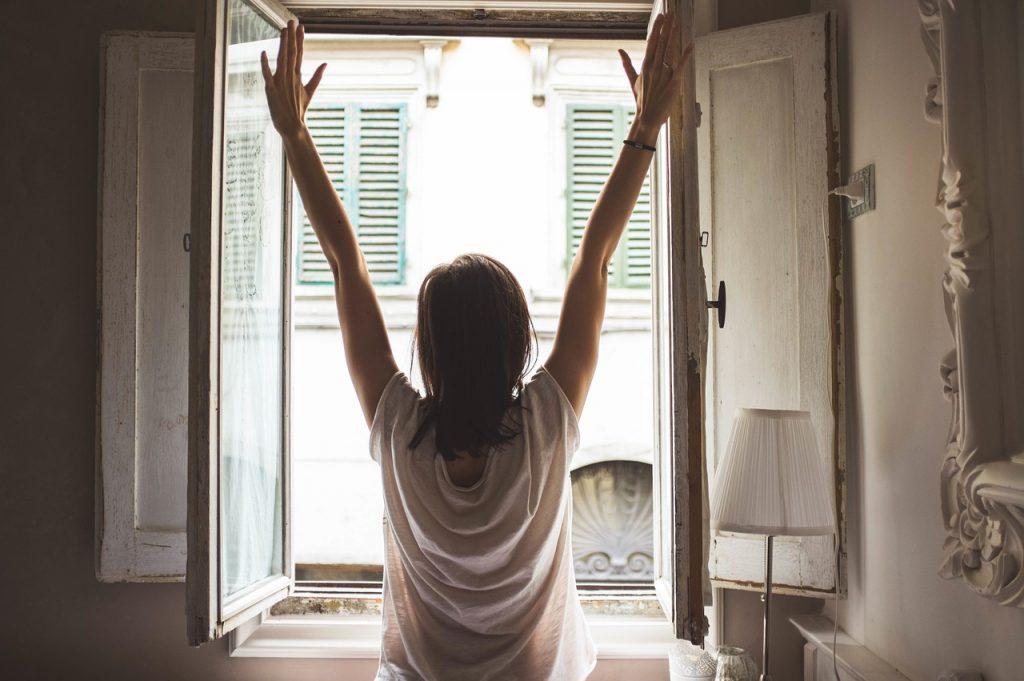 Žena se protahuje s rukama nad hlavou před otevřeným oknem