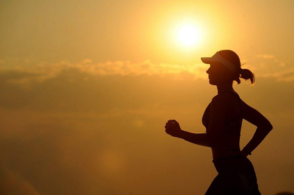 Silueta běžící ženy, v pozadí východ slunce
