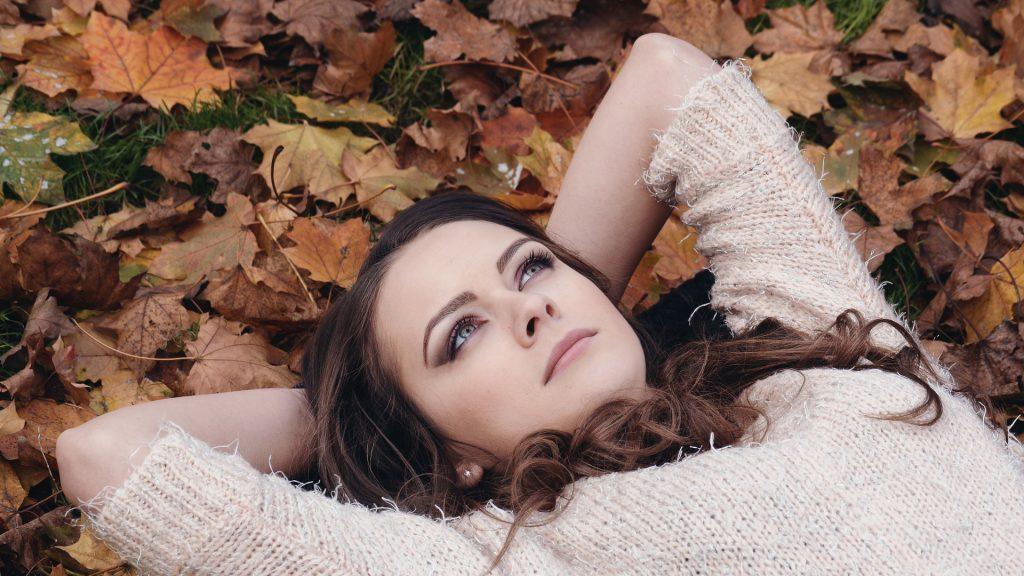 Dívka ležící ve spadaném listí